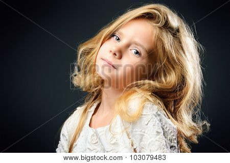 Close-up portrait of a pretty little girl with beautiful blonde hair wearing white dress. Studio shot. Kid's beauty, fashion.