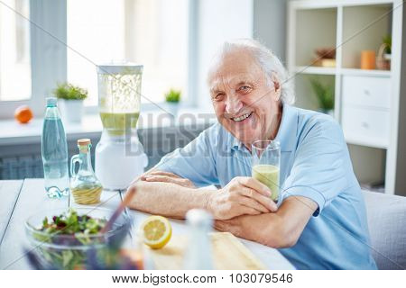 Senior man with glass of fruit smoothie sitting in the kitchen