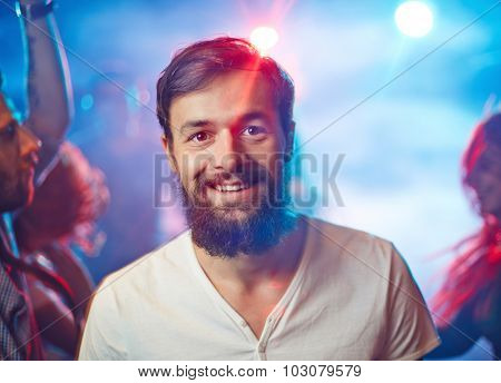 Happy unshaven man looking at camera with smile during party in night club