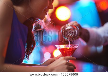 Girl looking at drink in martini glass while barman pouring cocktail for her