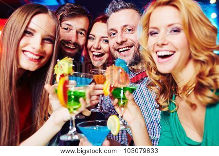 Ecstatic young people with cocktails cheering at party