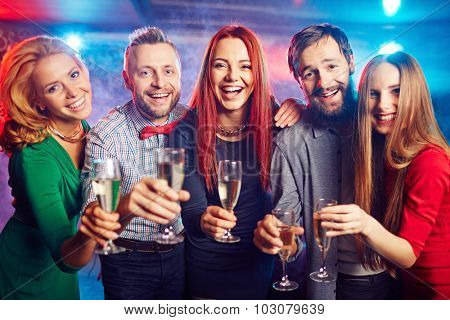Cheerful friends with flutes looking at camera at party in night club