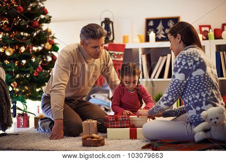 Family of three packing gifts and tying knots on tops of boxes before Christmas