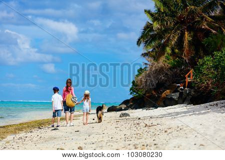 Active family of mother and kids walking along a tropical beach with their dog enjoying summer vacation