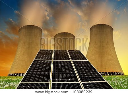 Solar energy panels before a nuclear power plant at sunset