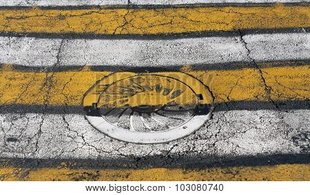 Manhole Cover On Yellow And White Pedestrian Crossing.