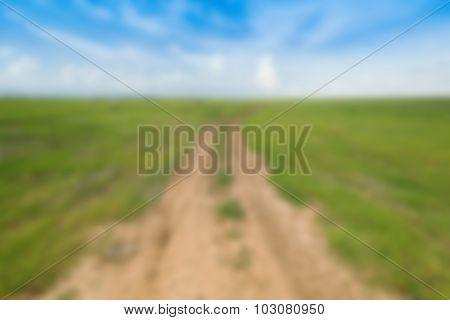 Blur Image Of Soil Road Between Grass Field