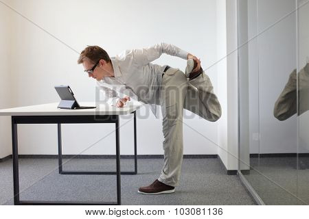 leg exercise during office work - standing man reading at tablet in his office