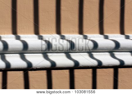 Metal Gate Shadow On Decorative Plaster Wall Texture.