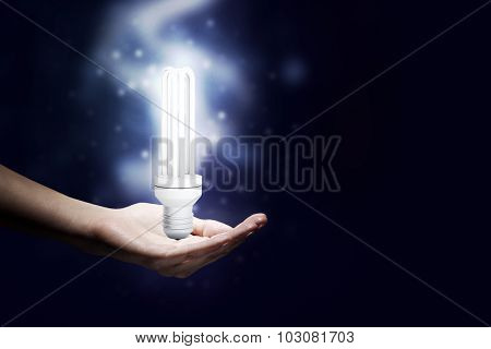 Close up of hand holding glowing light bulb