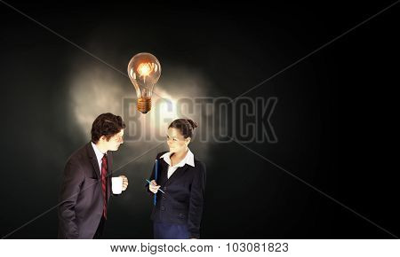 Partnership concept with businessman and businesswoman and glowing light bulb