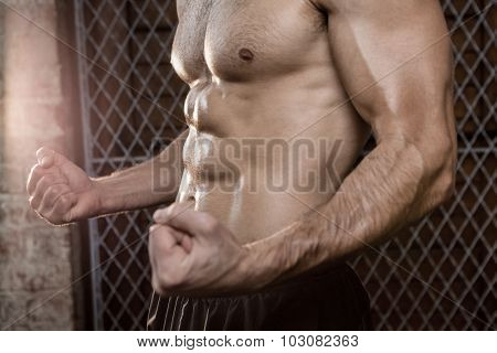 Midsection of muscular man with clenched fist at the gym