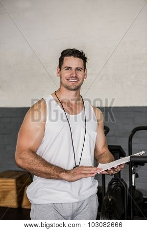 Portrait of instructor holding clipboard at the gym