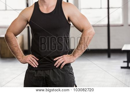 Midsection of man with hands on hip at the gym