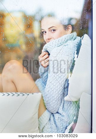Beautiful young smiling brunette woman wearing knitted dress sitting home behind a window covered with rain drops. Blurred fall garden reflection on the glass