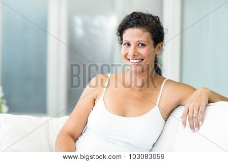 Portrait of pregnant woman sitting on sofa at home