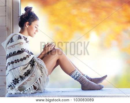 Young beautiful brunette smiling woman with cup of coffee wearing knitted nordic print poncho sitting home by the window. Blurred garden fall background.