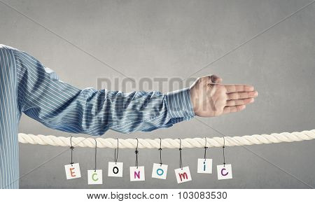 Word economic composed of cards hanging on rope and hand gesture