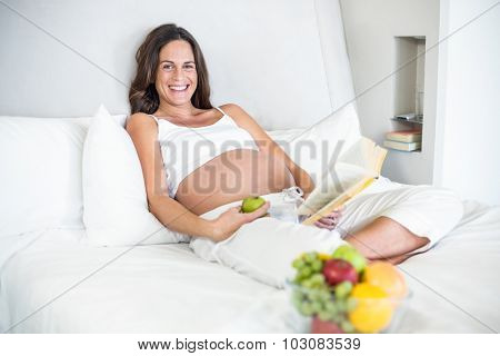 Portrait of happy pregnant woman with novel and Granny Smith relaxing on bed
