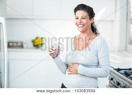 Happy pregnant woman holding a glass of water while standing in the kitchen