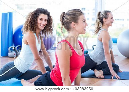 Women smiling while doing pigeon posture in fitness studio
