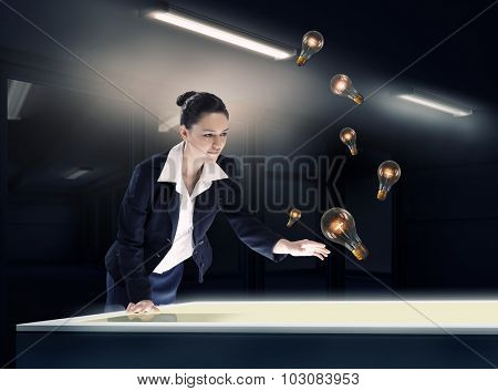 Young businesswoman catching glass light bulb with fingers
