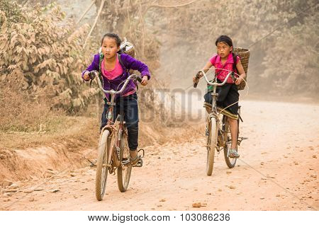Vang Vieng, Laos - January 26: Young Unidentified Girls Cycling Back From School On A Dusty Road