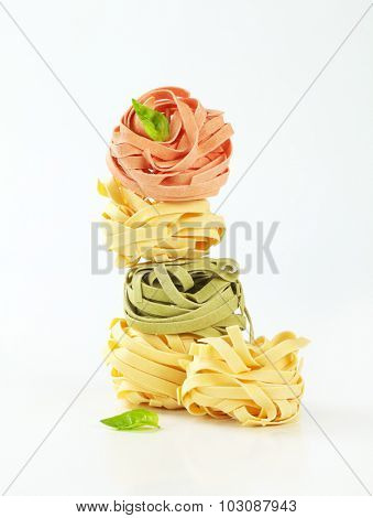 stacked pieces of dry pasta with different flavor and decorated with fresh leaves of basil