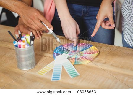 Midsection of colleagues pointing towards multi colored flow charts on desk in office