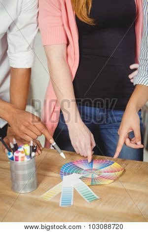 Midsection of colleagues pointing towards multi colored flow charts on wooden table in office