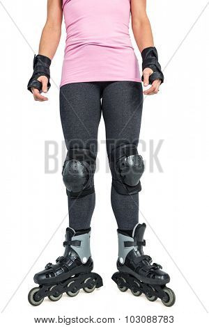 Low section of sporty woman inline skating against white background