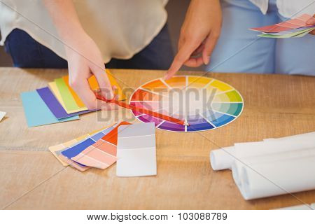 Midsection of colleagues pointing on multi colored flow charts on desk in office