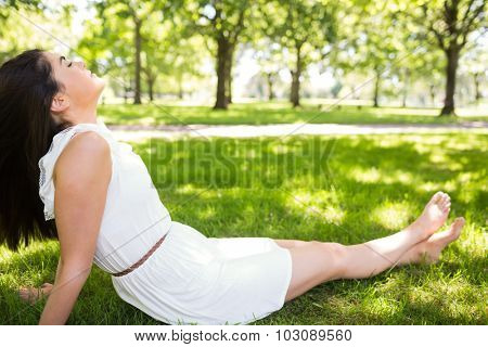 Pretty woman relaxing with eyes closed while sitting on grassland