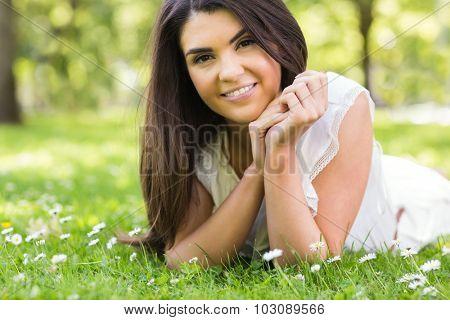Portrait of pretty woman lying on green grassland in park