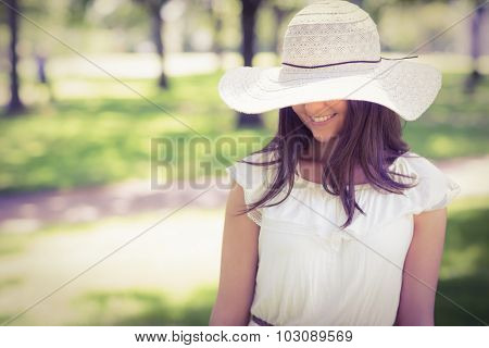 Smiling young woman in sun hat standing on grassland in park