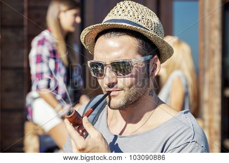 young hiker lights his pipe in front of the hut