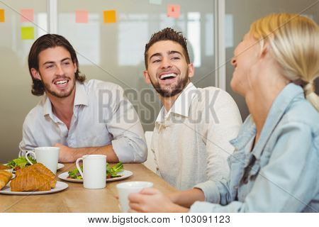 Business people laughing during brunch in creative office