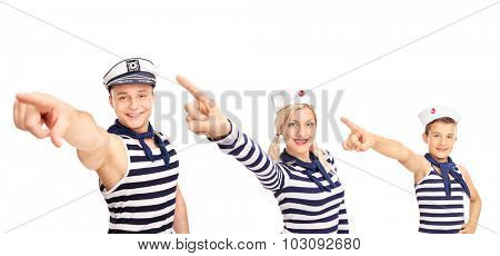 Man, a woman and a child in sailor outfits pointing forward with their hands and looking at the camera isolated on white background
