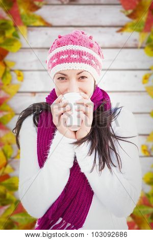 Winter brunette with coffee against autumn leaves on wood