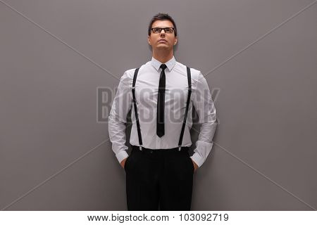 Confident young man in elegant outfit leaning against a gray wall and looking up