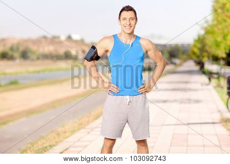 Male athlete listening to music on his cell phone and standing on a sidewalk