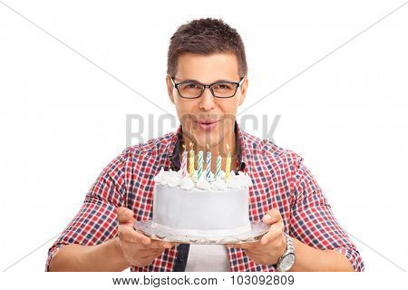 Joyful young man blowing candles on a birthday cake and looking at the camera isolated on white background
