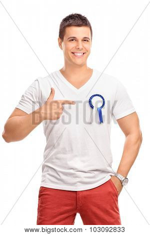 Studio shot of a joyful young man wearing a blue award ribbon on his shirt and pointing towards it with his hand isolated on white background