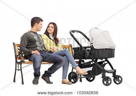 Young parents sitting on a bench and talking to each other with a baby stroller next to them isolated on white background