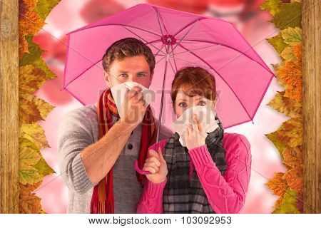 Couple standing underneath an umbrella against autumn scene
