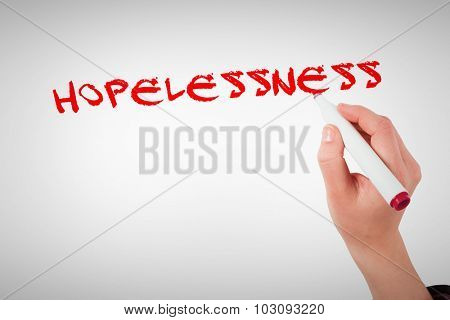 The word hopelessness against businesswomans hand writing with marker