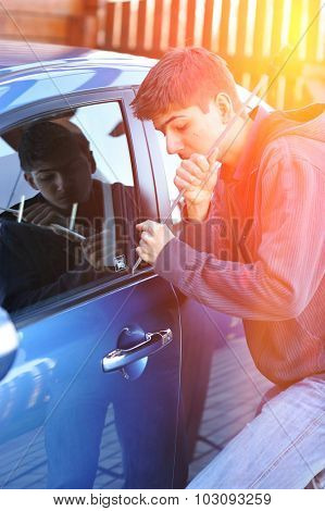 Young man trying to steal a car