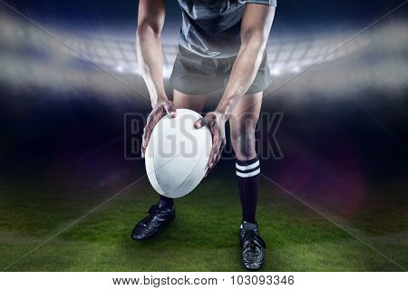 Low section of athlete holding rugby ball against rugby stadium