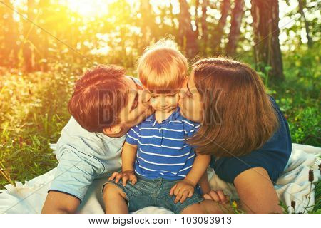 Happy family outdoors. Parents kissing their child.