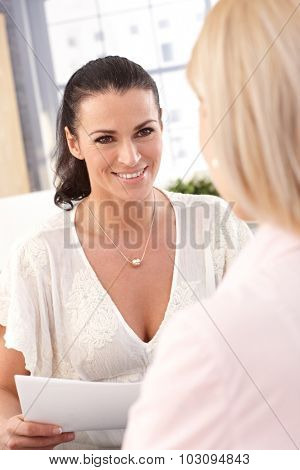 Close up of happy female casual brunette office worker with business papers, smiling.